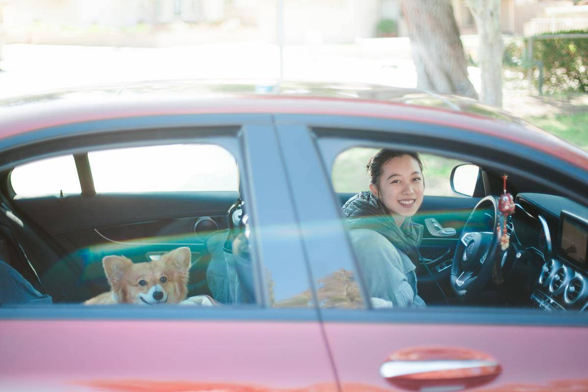 a girl parked in a red car with a corgi in the backseat