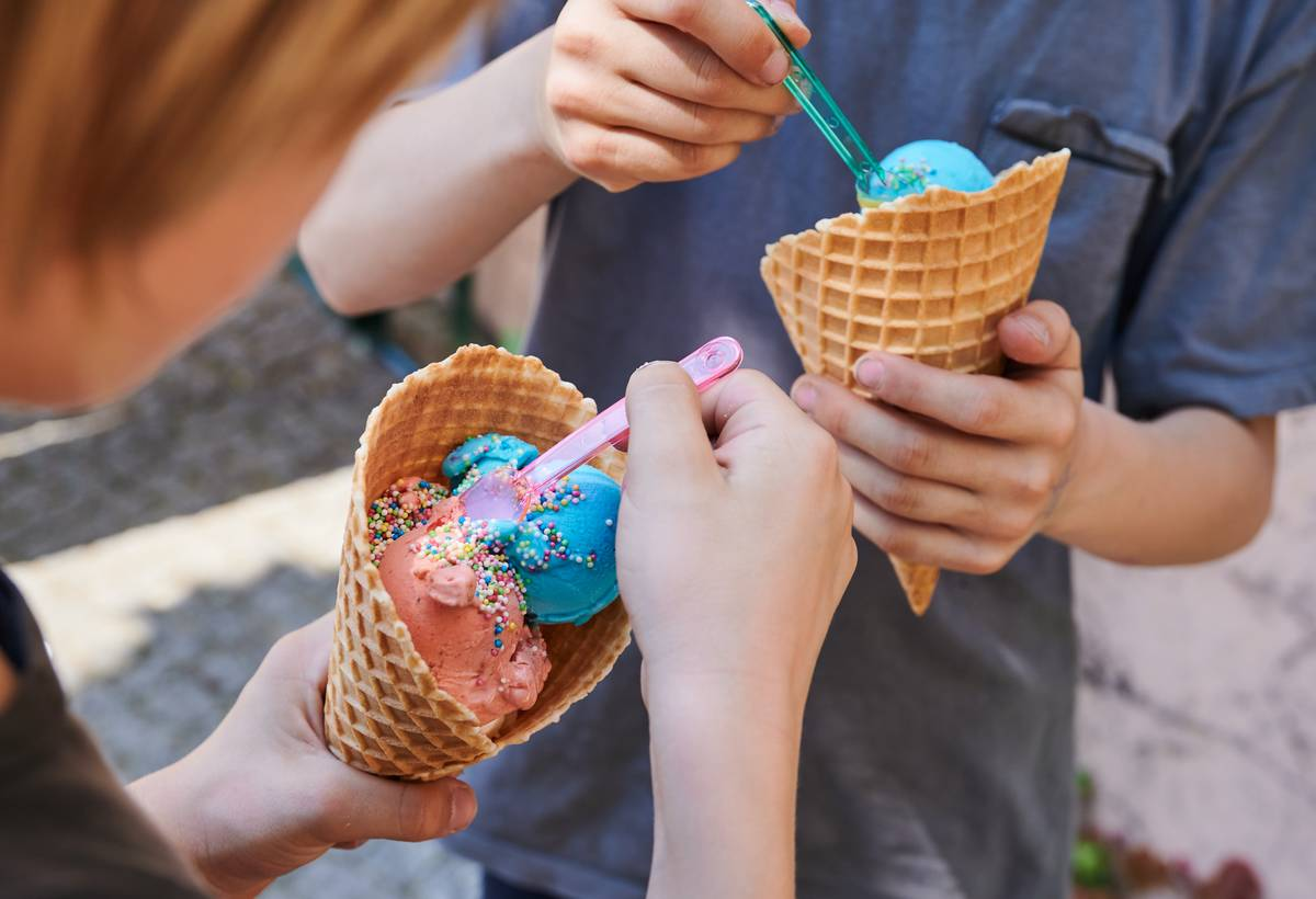 Two kids eat colorful ice cream out of cones.