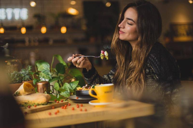 A woman smiles as she eats pasta salad.