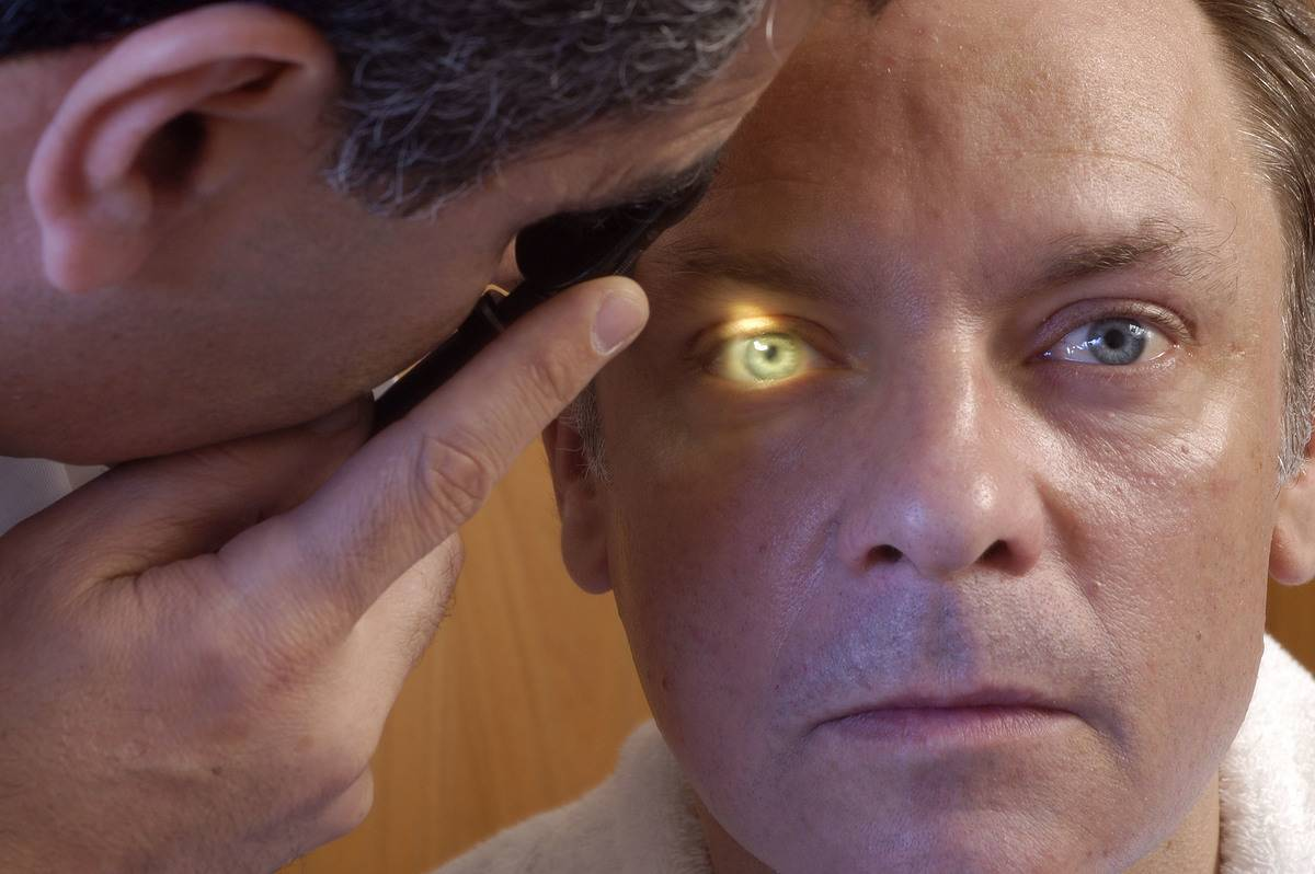 A doctor shines a light in a man's eye during an Ophthalmology Exam.