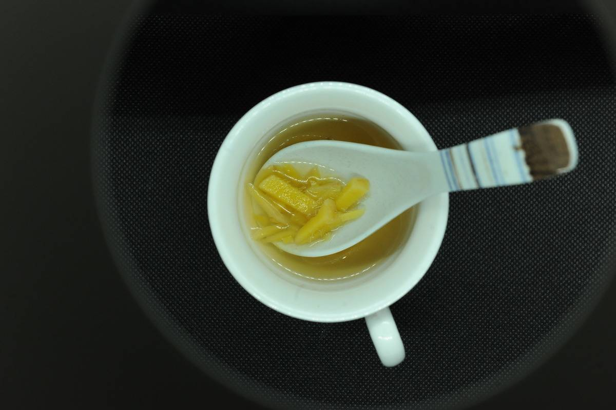 A spoon digs out chopped ginger from a cup of tea.