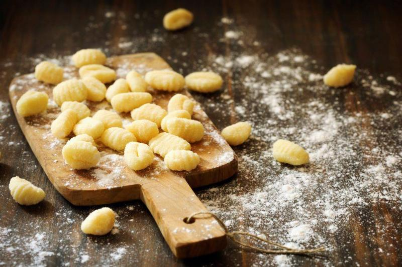 uncooked homemade potato gnocchi with flour on a wood paddle