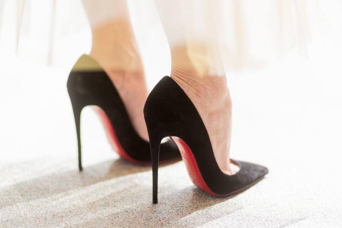 A woman wears tall heels.