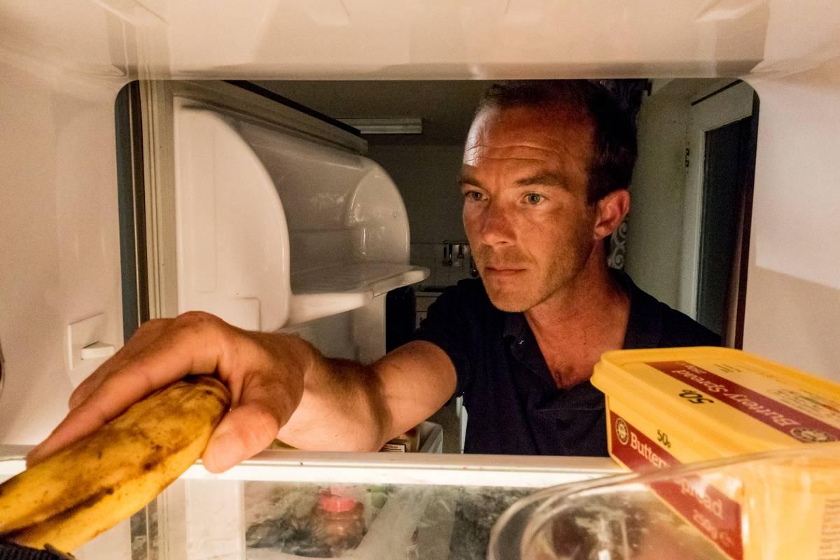 A man reaches into the fridge for a banana.