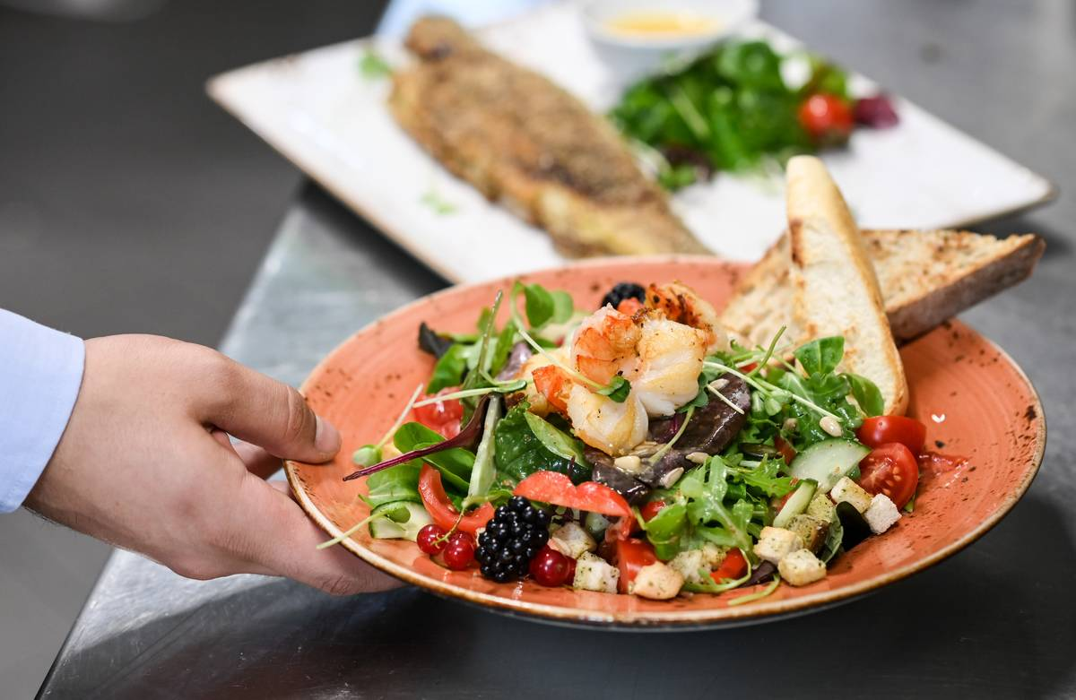 A server puts a plate of salad, trout, and bread onto a restaurant table.