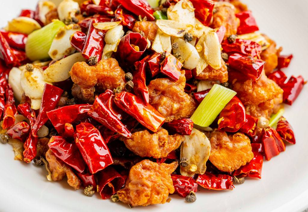 orange chicken with red chili peppers and scallions on a plate