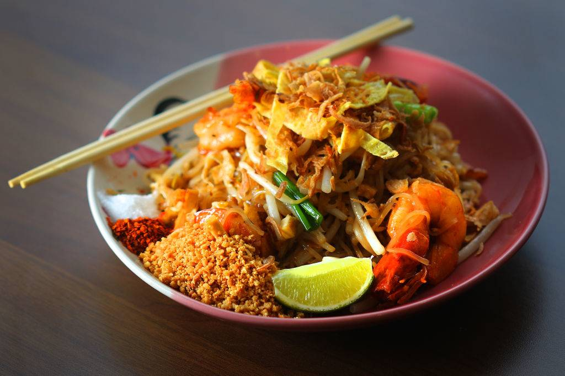 pad thai with grains, shrimp, a lime slice, and chopsticks