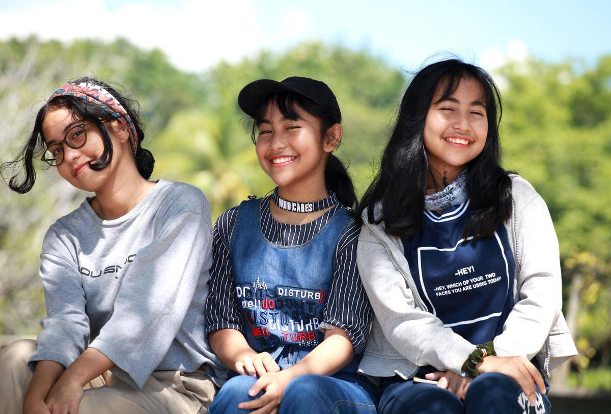 three girls sitting outside