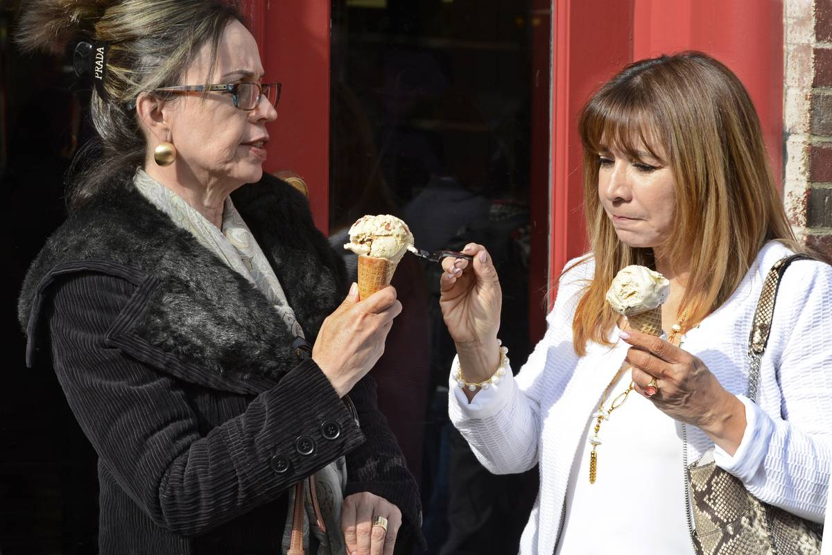 A woman shares her ice cream cone with her friend.