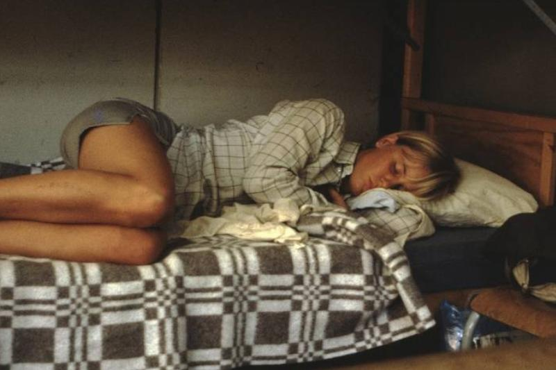 A woman sleeps on the bottom bunk of a bunk bed.