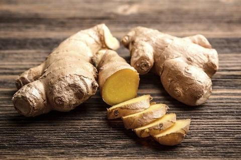 Part of a fresh ginger root is sliced into pieces.