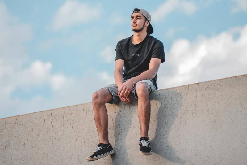 a man sitting on a wall with legs spread out