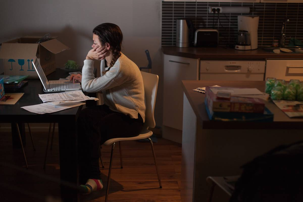 At night, a woman works on her taxes with her laptop.