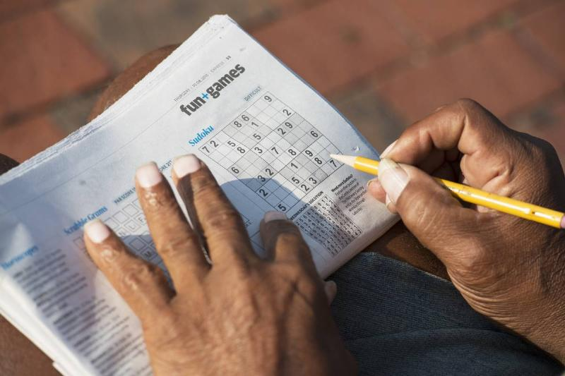 A man does a sudoku puzzle in the newspaper.