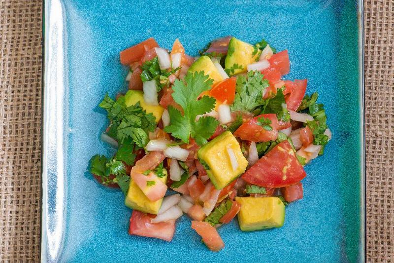 chopped up avocado, cilantro, tomatoes, and onions on a blue plate