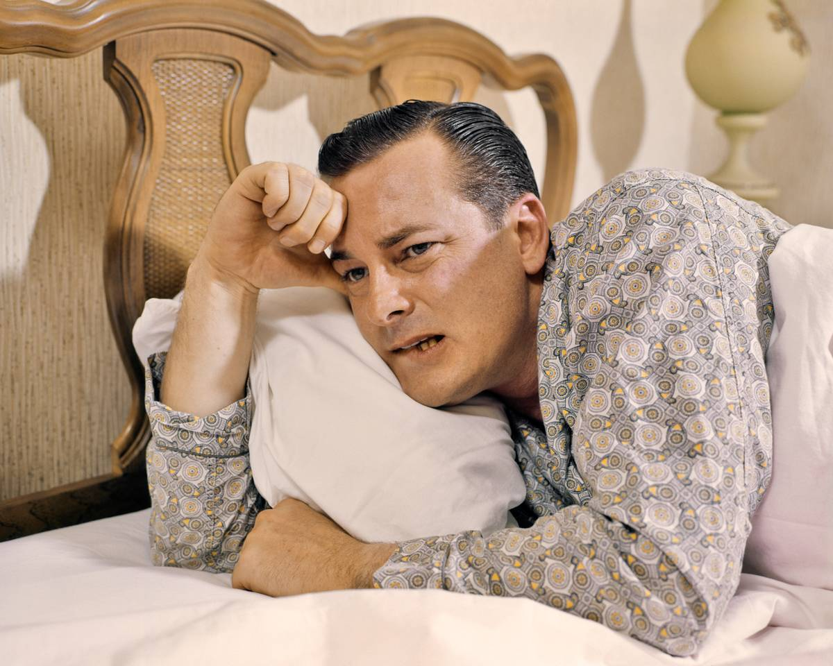 A man sits up in bed, tired and groggy.