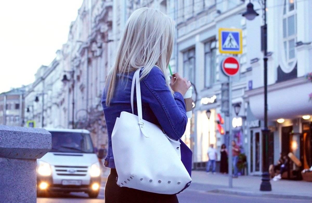 A woman walks through a city while carrying a purse.