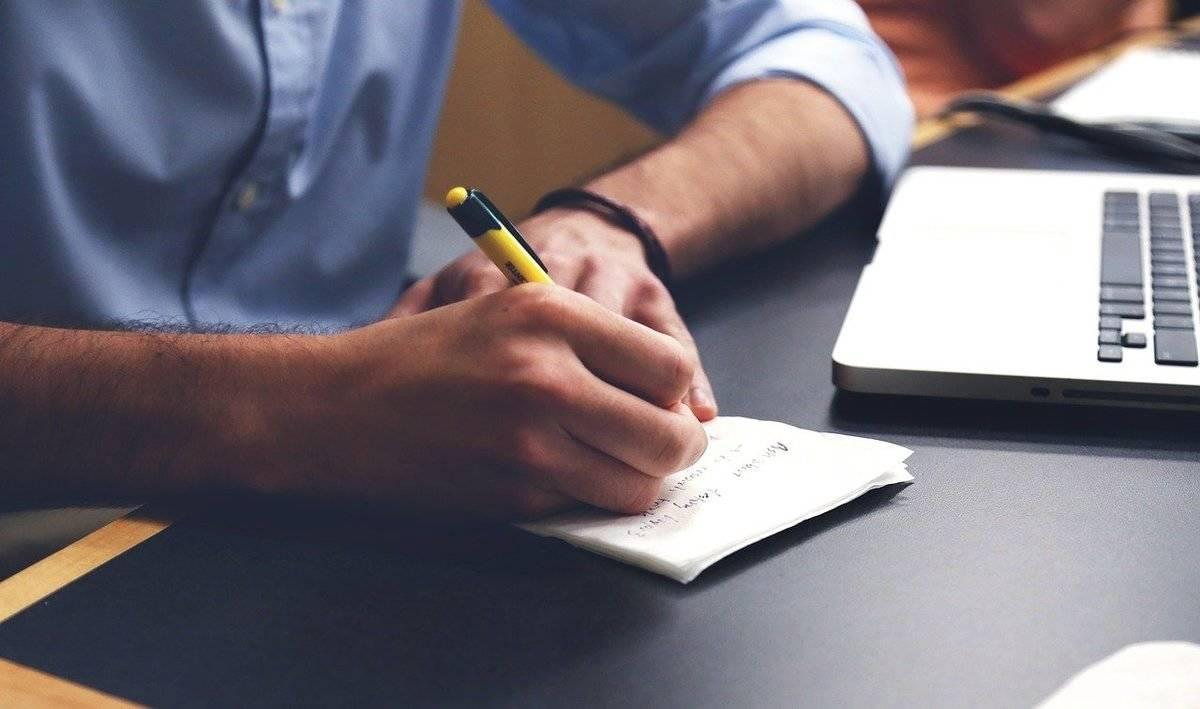 A man writes on a notepad.