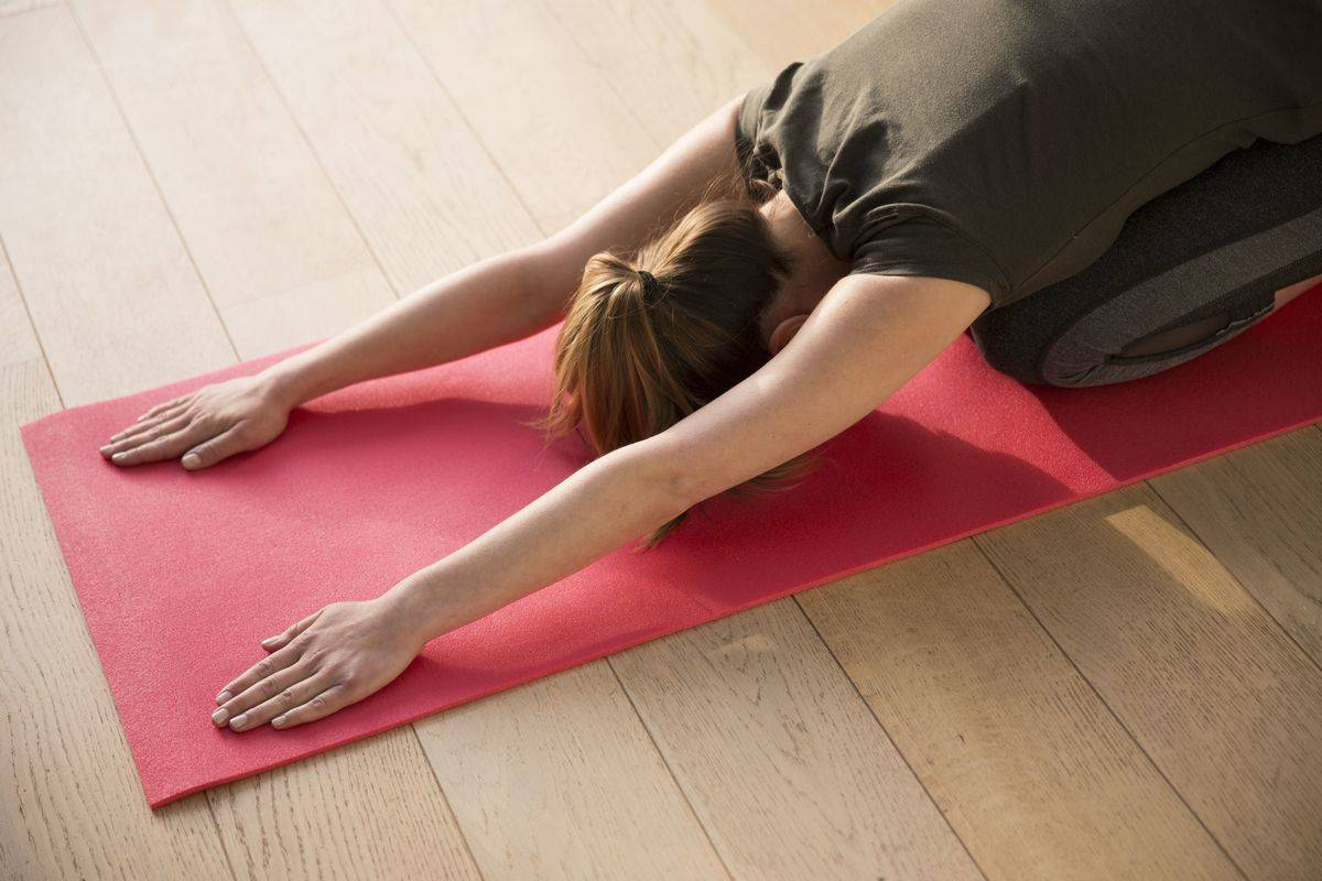 A woman does a yoga stretch on her mat.