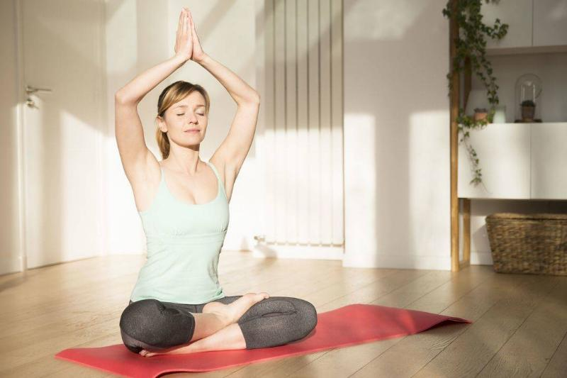 A woman practices yoga in her bedroom.