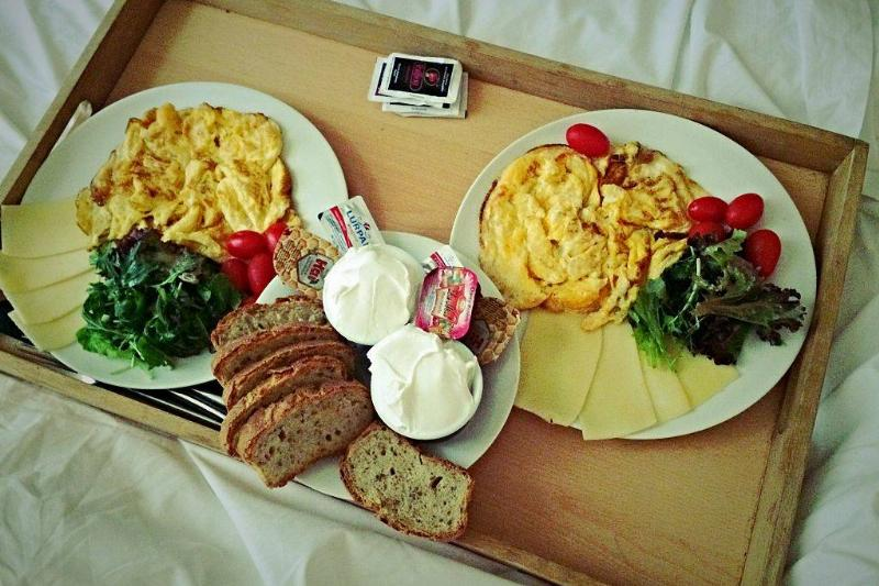plates with eggs, tomatoes, salad, cheese, bread, and butter in bed