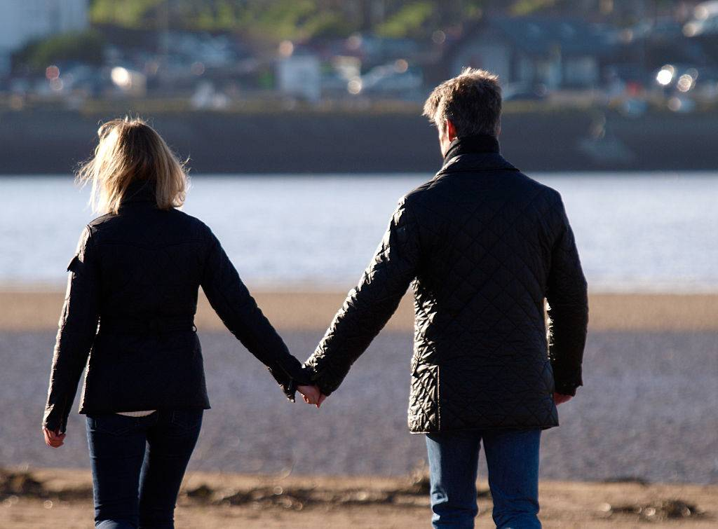 Middle aged couple holding hands