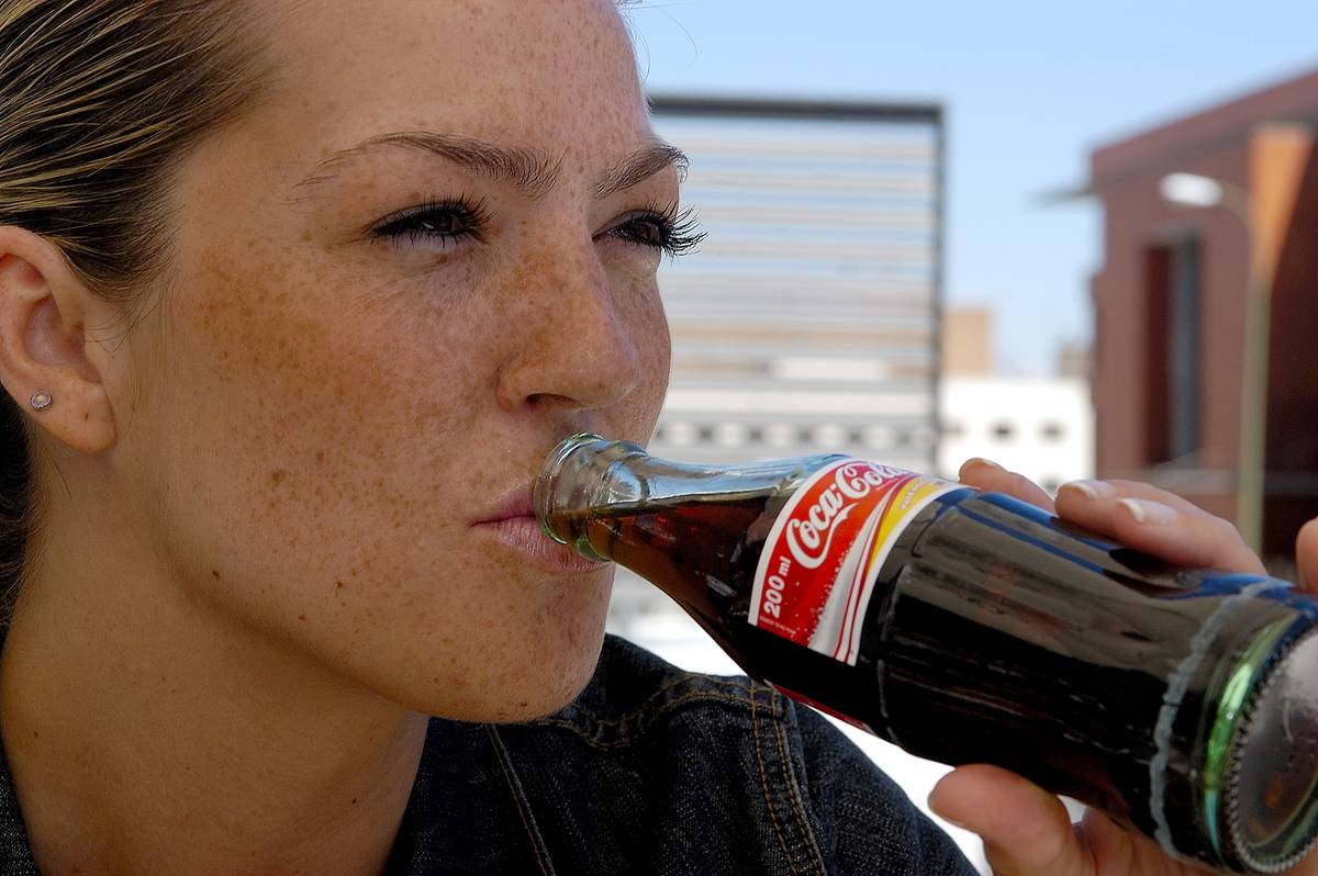 A woman drinks from a coca cola bottle.
