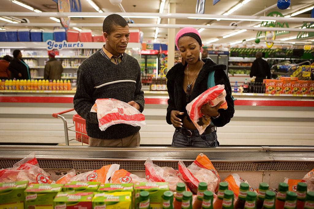 A young couple do their weekly shopping at a large supermarket