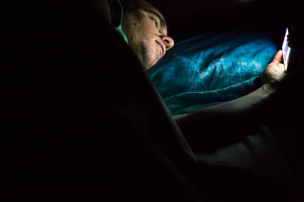 A man scrolls through his iPhone while lying in bed in the dark.