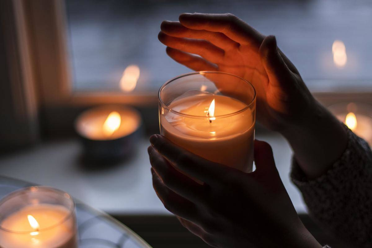 A person holds a lit scented candle.