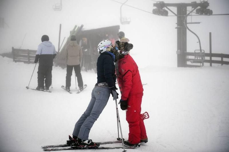 A couple kiss as they join skiers and snowboarders braving the winter conditions