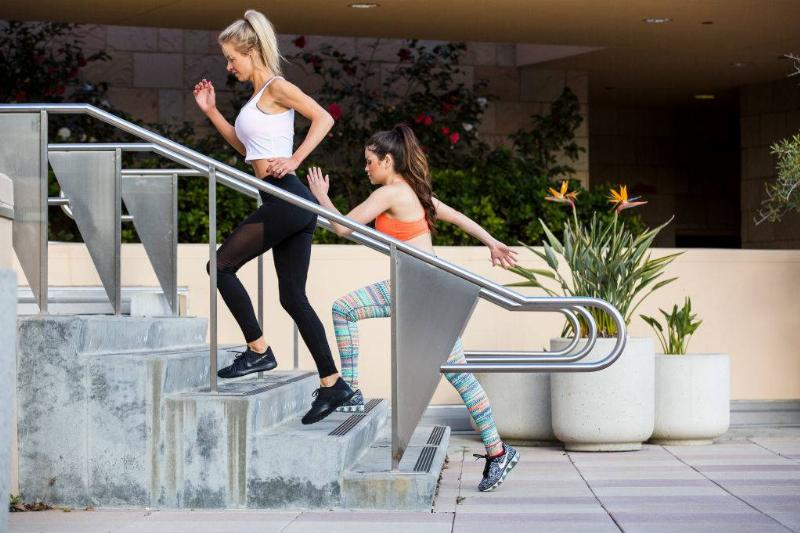 two women running up some stairs outside