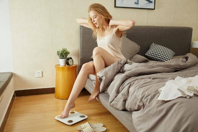 A woman gets out of bed and immediately steps onto a scale.