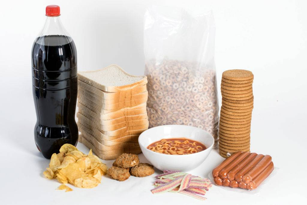 processed food with soda, bread, cereal, crackers, hot dogs, candy, chips, chicken nuggets, and spaghetti o's