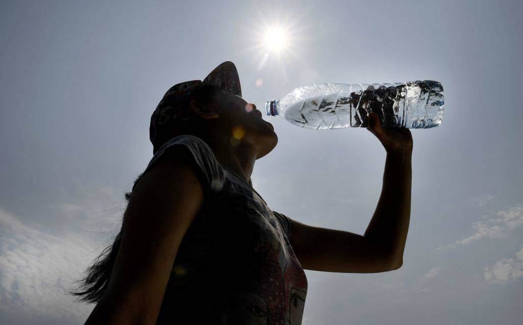 A woman drinks water from a plastic bottle