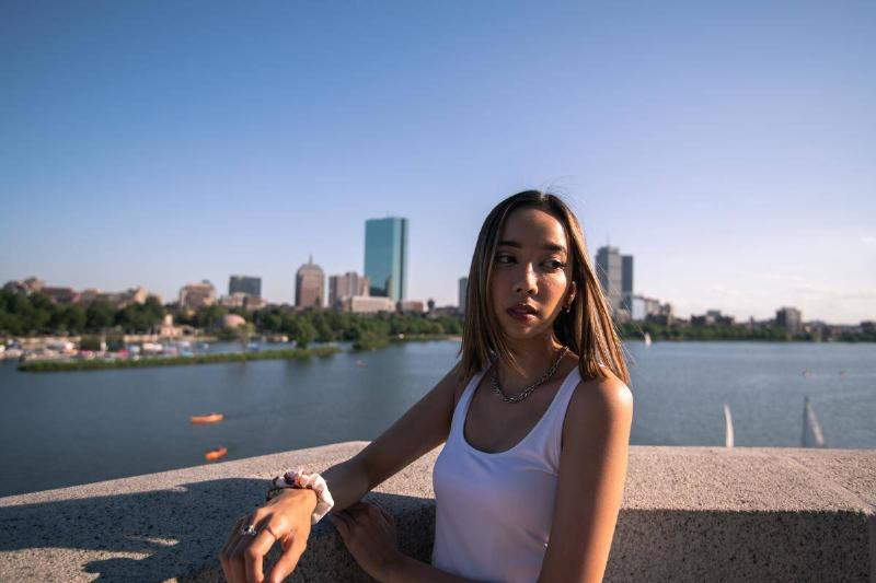 girl standing by the water and skyline in boston
