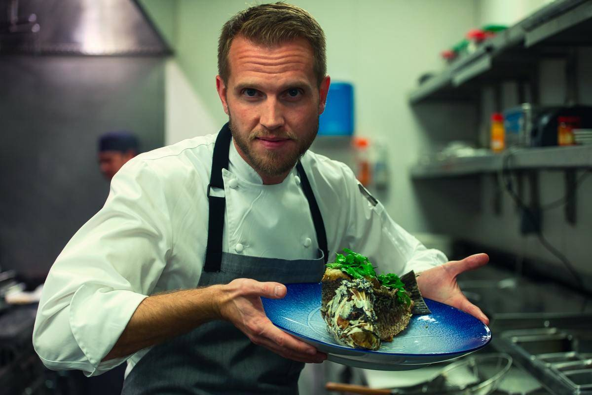 a chef holding up a dish