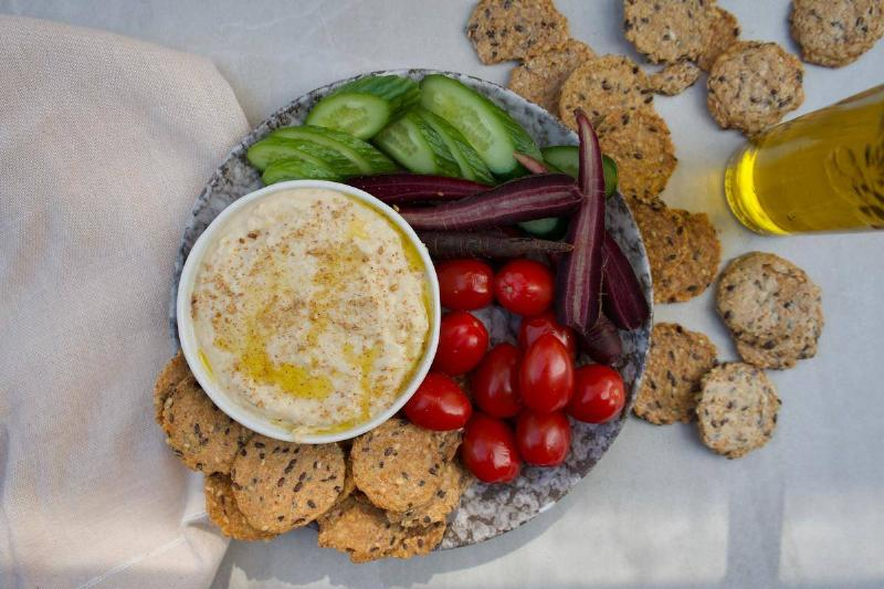 hummus on a plate with crackers, cucumbers, purple carrots, and cherry tomatoes