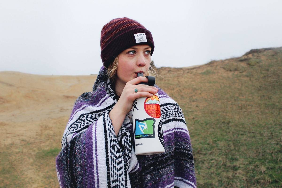 a young woman drinking water out of a reusable water bottle