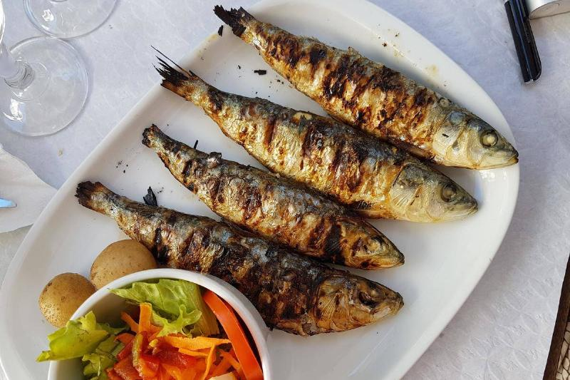 cooked fish with a side salad