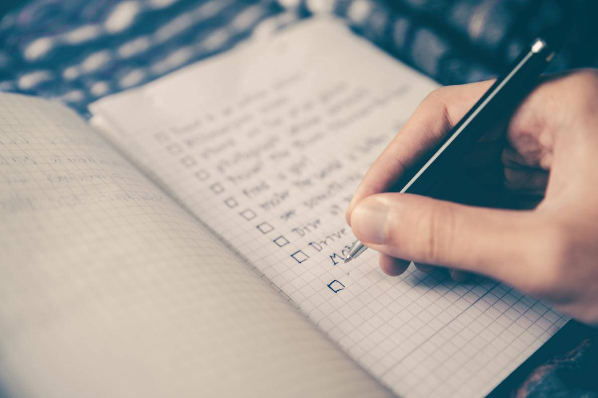 person writing a checklist