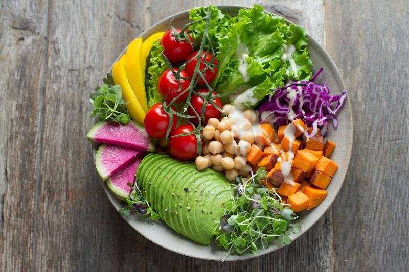 a salad with avocado, tomatoes, garbanzo beans, cabbage, sweet potato, peppers, and sprouts