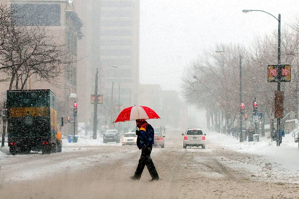 A man holds an umbrella as he crosses a street in Milwaukee, Wisconsin