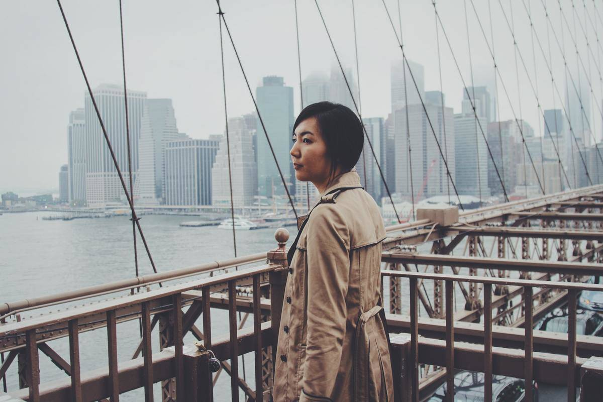 a woman standing on a bridge in new york city