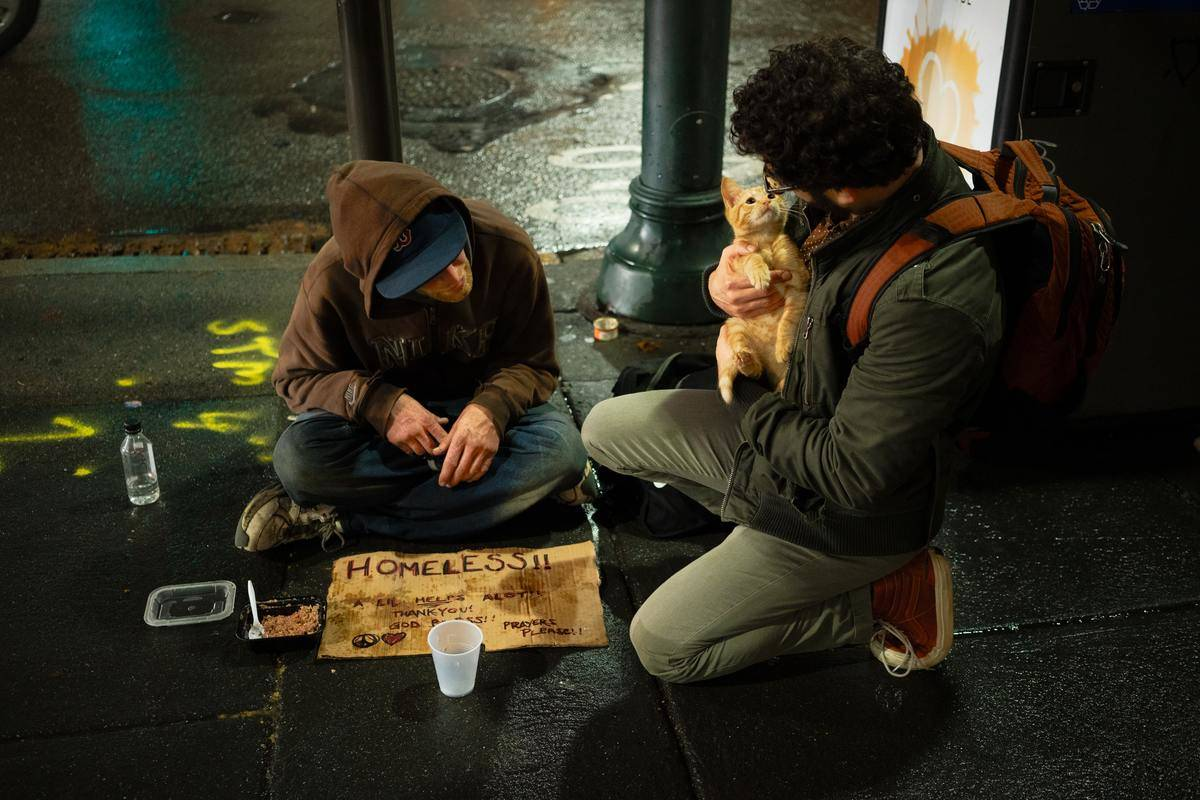 a homeless man greeted by another man holding a tabby cat